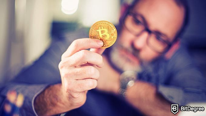 How does Bitcoin work: a man holding a Bitcoin.