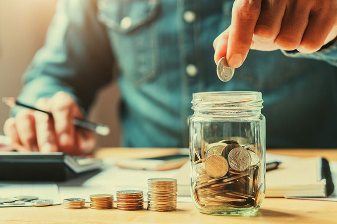 What is a cryptocurrency: a man placing coins into a jar.