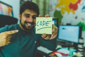 Computer science salary - holding a sticknote with word code