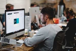 man in a grey sweater doing graphic design on a mac