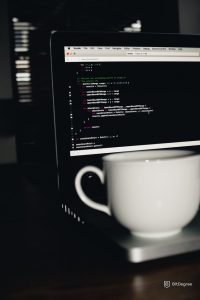 cup in front of laptop